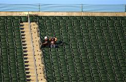Two fans watch the Seattle Seahawks take on the Oakland Raiders at Oakland-Alameda County Coliseum during the preseason. The Raiders had seven TV blackouts last year.
