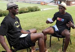 Cincinnati Bengals wide receivers Terrell Owens, left, and Chad Ochocinco asks each other questions during a TV taped interview during training camp on Aug. 11. They're bring their gift for gab to their new TV show, 'The T.Ocho Show' on Versus.