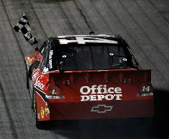 Tony Stewart celebrates with the checkered flag after winning Sunday night at Atlanta Motor Speedway. The victory snapped a 31-race winless streak and gives Stewart some much-needed momentum heading into the Chase for the Sprint Cup.