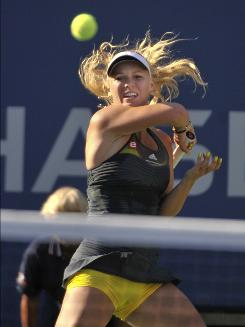 Top-seeded Caroline Wozniacki of Denmark withstood her toughest test of the tournament on Monday, topping Maria Sharapova 6-3, 6-4 in the fourth round of the U.S. Open. Wozniacki can take over the No. 1 ranking if she wins her first major title.