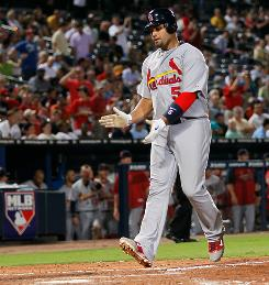 Albert Pujols crosses home plate after hitting his 37th home run in the fourth inning against the Braves.