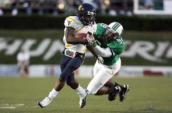 West Virginia running back Noel Devine tries to elude the grasp of Marshall defender Grady Kerr as the Mountaineers improved to 10-0 over their rivals.