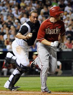 Rockies catcher Miguel Olivo runs down Arizona Diamondbacks shortstop Stephen Drew during the seventh inning of Colorado's 2-1 win, their ninth in a row.