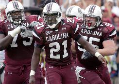 South Carolina's Marcus Lattimore (21) celebrates with his teammates after scoring his second touchdown against Georgia.