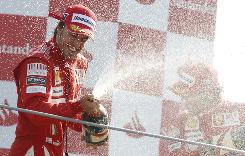 Fernando Alonso sprays champagne on the podium after winning the Italian Grand Prix in Monza, Italy.