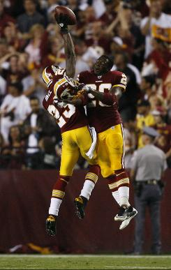 Redskins cornerback DeAngelo Hall, left, and running back Clinton Portis celebrate Hall's touchdown on a fumble recovery on the final play of the first half. The score was Washington's only touchdown of the game, but it proved to be enough as the Redskins defeated the archrival Cowboys 13-7 in the season opener.