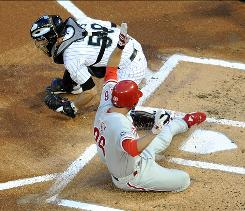 The Phillies' Chase Utley slides past Marlins catcher Brad Davis to score a run in the first inning. Utley also led off the third with his 15th home run.