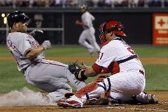 The Nationals' Ivan Rodriguez, left, is tagged out at home by Phillies catcher Carlos Ruiz in the fourth inning of their game Friday in Philadelphia. The Phillies won 9-1 behind another strong outing by Roy Oswalt.