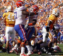 Florida running back Mike Gillislee (23) is congratulated by guard Carl Johnson (57) after Gillislee scored the game's first touchdown on a 2-yard run.