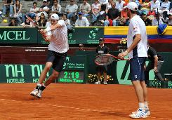 Mardy Fish watches as U.S. teammate John Isner swings through a return during their doubles match against Colombia.