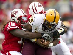Wisconsin defender Culmer st. Jean (15) holds back Arizona State running back Cameron Marshall as the Badgers edged out the visiting Sun Devils.