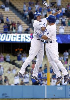Los Angeles catcher A.J. Ellis, right, celebrates with Andre Ethier after hitting the game-winning single to score Rafael Furcal in the bottom of the 11th inning to give the Dodgers a 7-6 victory over the Colorado Rockies.
