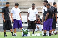 West Orange-Stark High School teammates of Reggie Garrett, the quarterback who died after collapsing on the sidelines during Friday's game, visit a memorial placed at the spot where Garrett fell at Dan Hooks Stadium in West Orange, Texas