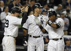 The Yankees' Francisco Cervelli, left, and Derek Jeter, center, celebrate with Curtis Granderson after scoring on Granderson's three-run homer in the sixth-inning. Granderson also hit a two-run homer in the third.