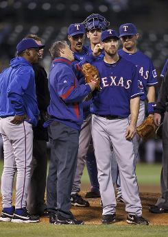 Rangers starting pitcher Cliff Lee is attended to by a trainer after a play involving a splintered bat. Lee struggled while A's pitcher Dallas Braden shined in Oakland's 5-0 win.