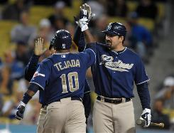 Padres shortstop Miguel Tejada, left, is congratulated by first baseman Adrian Gonzalez after hitting a two-run home run in the third inning. The shot was Tejada's eighth since joining San Diego.