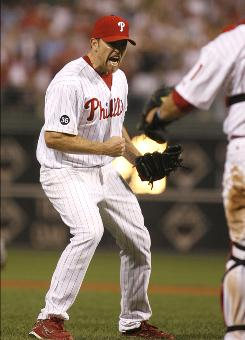 Phillies pitcher Brad Lidge celebrates after striking out the Mets' Jesus Feliciano in the bottom of the ninth inning to close out the team's 11th consecutive win.