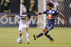Red Bulls midfielder Mehdi Ballouchy, right, and Galaxy midfielder Juninho battle for possession as New York tied Columbus for first place in the Eastern Conference with the road victory.