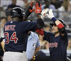 Boston's Jed Lowrie, right, gets a high-five from teammate David Ortiz after hitting a three-run homer during the second inning of the Red Sox's 10-8 win over the Yankees.