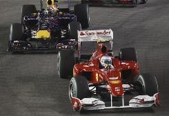 Ferrari's Fernando Alonso leads the Red Bull of Sebastian Vettel at the start of the Singapore Grand Prix.