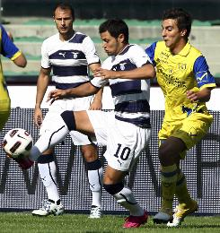 Lazio's Mauro Zarate fends off Chievo's Simone Bentivoglio during their match in Verona, Italy. Zarate scored the lone goal as Lazio moved into a tie for first in the Serie A standings.