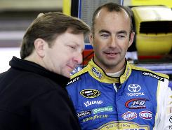 Marcos Ambrose, right, talks things over during practice at New Hampshire Motor Speedway.