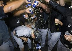 New York Yankees' team members dump their beers on Derek Jeter, center, after the Yankees defeated the Toronto Blue Jays 6-1 and clinched a baseball playoff berth.