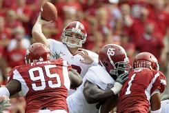 Alabama quarterback Greg McElroy, passing under an intense rush from Arkansas last Saturday, leads the top-ranked Crimson Tide against No.7 Florida this weekend.
