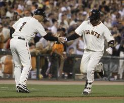San Francisco Giants' Juan Uribe, right, is greeted by third base coach Tim Flannery after hitting a home run off Arizona Diamondbacks starting pitcher Rodrigo Lopez during the fourth inning of the Giants' 4-2 win over the Diamondbacks.