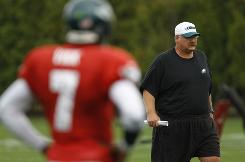 Eagles head coach Andy Reid walks near quarterback Michael Vick during practice on Wednesday.