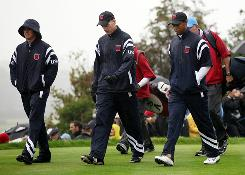 Rickie Fowler, left to right, Jim Furyk and Tiger Woods, all wrapped up in rain gear, walk the course Wednesday during a practice round for the Ryder Cup at Celtic Manor in Newport, Wales. Rain is in the forecast throughout the weekend.