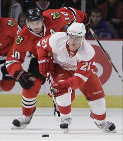 The Detroit Red Wings' Tomas Tatar, right, advances the puck as Chicago Blackhawks' Patrick Sharp pursues during the first period of their preseason NHL hockey game Saturday in Chicago.