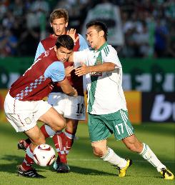 Aston Villa's Eric Lichaj, left, vies for the ball against Rapid Vienna's Veli Kavlak, right, during Europa League play in August. Lichaj left the University of North Carolina to sign with the English team in 2007.