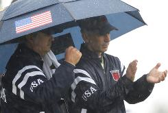 U.S. captain Corey Pavin, right, and assistant captain Paul Goydos seek shelter from the rain under an umbrells. Good thing they had the umbrella, since the rain gear the team brought along wasn't up to par.
