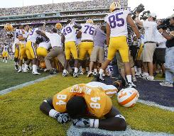 Tennessee defensive end Chris Walker is dejected as LSU players celebrate their win on the last play.