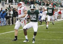 Michigan State wideout Keshawn Martin celebrates a touchdown in front of Wisconsin defensive tackle J.J. Watt during the second quarter.