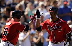 Braves first baseman Derrek Lee, right, is welcomed to homeplate by catcher Brian McCann after hitting a solo home run.