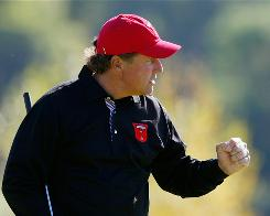 Phil Mickelson of the USA pumps his fist after knocking in a putt on his way to a 4 and 2 singles victory against Peter Hanson on Monday at the Ryder Cup.