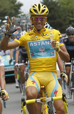 Alberto Contador flashes three fingers for his third Tour de France victory as he holds a glass of champagne during the last stage of the Tour de France this past summer.