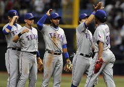 Rangers closer Neftali Feliz, far right, is congratulated by teammates after getting the final out in the ninth inning in Game 1 of the ALDS against the Rays.
