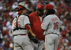 Reds starter Edinson Volquez, who gave up four runs in 1 2/3 innings, is removed from the game by manager Dusty Baker, center, as catcher Ramon Hernandez listens in.