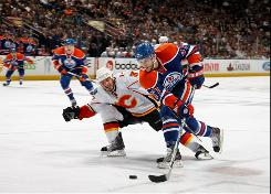 Ian White of the Calgary Flames checks Gilbert Brule, right, of the Edmonton Oilers during the first period.