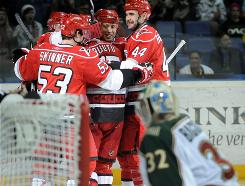 Tuomo Ruutu is surrounded by Hurricanes teammates after scoring the game-tying goal in the second period.