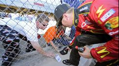 Jamie McMurray signs autographs as fans push items under the fence after he took the pole during Friday's qualifying for Sunday's Pepsi Max 400 in Fontana, Calif. The track has had two NASCAR events for several years but will only have one in 2011.