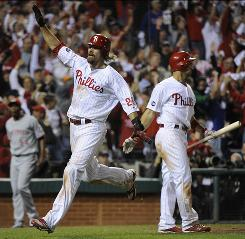 The Phillies' Jayson Werth (28) runs past teammate Raul Ibanez in the on-deck circle en route to scoring the go-ahead run in the seventh inning. The Phillies rallied to beat the Reds 7-4.