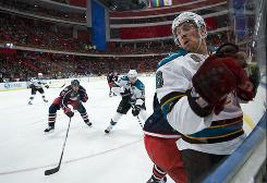 The Sharks' Joe Pavelski, right, gets body checked by the Blue Jackets' Marc Methot during the teams' season opener Friday at the Globe Arena in Stockholm. San Jose beat Columbus 3-2.