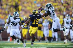 Michigan State cornerback Chris Rucker has been suspended for one game for an unspecified violation of team rules. Here, Rucker (29) intercepts a pass intended for Michigan  wide receiver Kelvin Grady (19) during the fourth quarter on Saturday.
