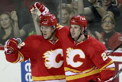 Curtis Glencross, right, celebrates his short-handed goal with Brett Sutter. The Flames' first goal of the season was scored midway through the second period of their second game.