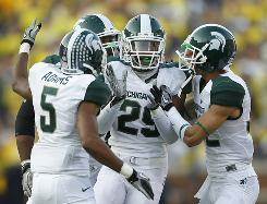 Michigan State defenders celebrate one of their three interceptions of Michigan quarterback Denard Robinson during the Spartans' victory in Ann Arbor.