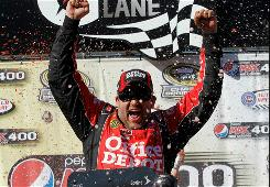 Tony Stewart celebrates in victory lane after winning the Pepsi Max 400 on Sunday. Clint Boyer and Jimmie Johnson took second and third, respectively, at the Sprint Cup event.